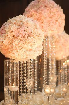 gorgeous white carnation ball and crystal centerpieces. Place the ball on a clear vase and pin crystals to the bottom of the ball, so that they can hang down inside. Use a flameless votive candle inside the vase. Brilliant!