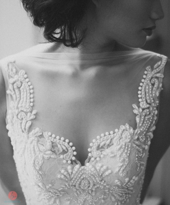 Illusion neckline on a wedding dress. The fake neckline is heavily ornamented, detracting from the gauze above it. It keeps the middle between the sweetheart and square shape. (Veluz Reyes)