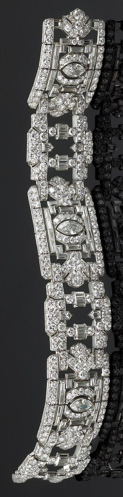 A late Art Deco diamond bracelet of flexible design, the three geometric panels each centring a marquise-cut diamond, surrounded by baguette and round brilliant-cut diamonds within an openwork frame, further enhanced by diamond set links of bullet-shaped diamonds and arched diamond spacers; estimated total diamond weight: 23.10 carats; mounted in platinum. #ArtDeco