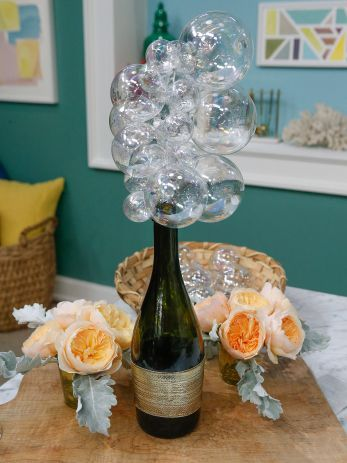 "Champagne Bottle Centerpieces. Remove labels from used champagne bottles. Needle-nosed pliers to cut wire coat hangers to  measures the bottom (straight edge) of the hanger + a curved portion. Straighten wire & shape. Make almost closed hook at end to hold bubbles. Thread round, glass opalescent of varied sizes onto the hanger pieces, starting with the smallest and alternating the sizes. Now you have ""bubbles"" for the Champagne Bottle Centerpiece."