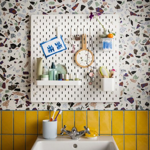 A bathroom wall with a white pegboard shown together with accessories in white lacquered steel, such as a shelf, containers, clips and hooks.