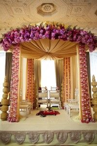 A pretty gold and pink stage for the wedding ceremony at an Indian wedding. The flowers are beautiful here!