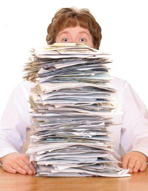człowiek za stertą dokumentów