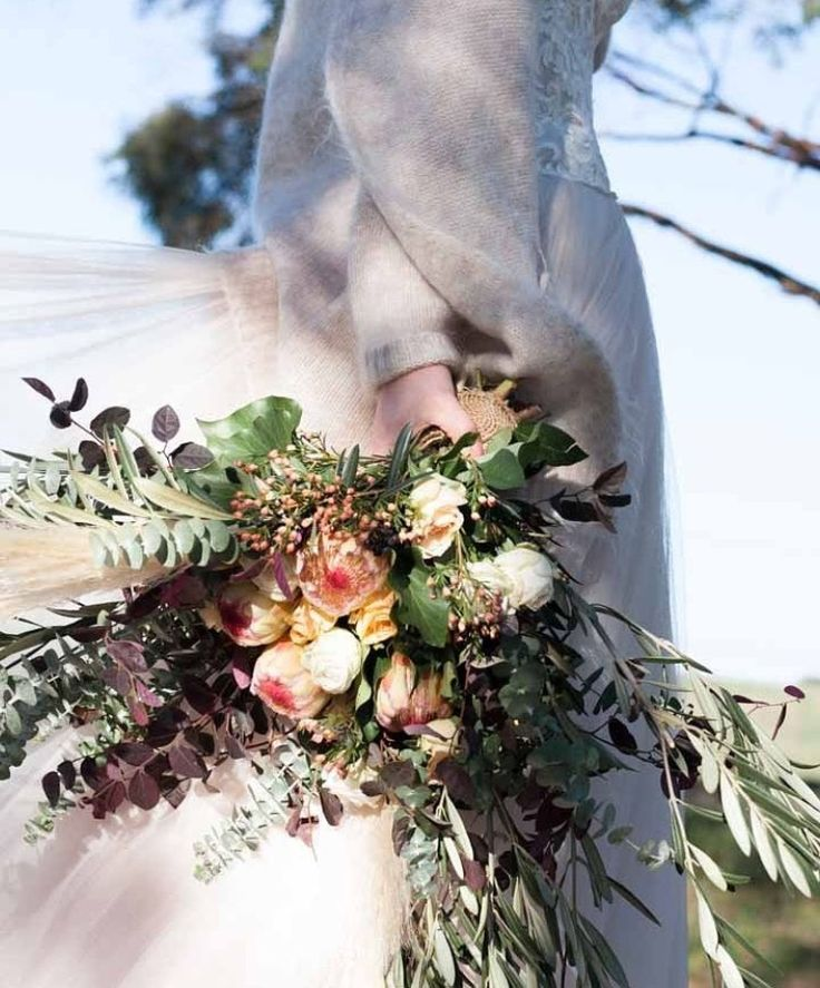 Wedding bouquet by Bettie bee blooms Photo by: @alexphotoandfilm King proteas, unstructured, native bouquet, burgundy, boho