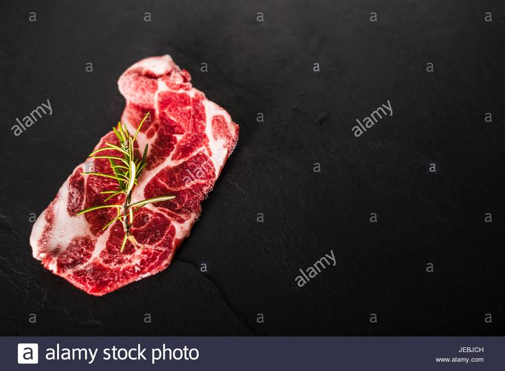 Download this stock image: Pork loin beef ready to grill over a dark black stone plate, studio shot. - JEBJCH from Alamy's library of millions of high resolution stock photos, illustrations and vectors.
