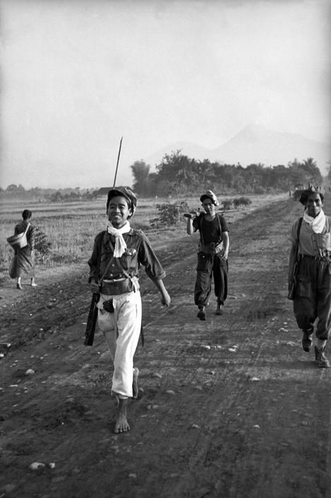 INDONESIA. 1949. A squadron of PNI guerilla fighters coming in from the mountains for a day in town. Some had no shoes but rifles, some rifles, but no shoes. From Magnum Photos website.