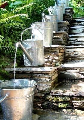Progressive waterfall from watering cans n steps. Outdoor.