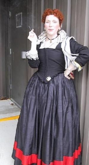 """this is a middle-class outfit of roughly 1590.     My hair is curled (""""fryssed"""") to create the high effect popular at the time, and dyed red because I like it that way, and it's a very fashionable Elizabethan colour (you can take my dye away from me when you pry it from my cold dead fingers).    I'm wearing a high-necked shift that was machine-embroidered (made many years ago) in simple straight lines in an attempt to get people to see that they could get an """"embroidered"""" look without using…"""