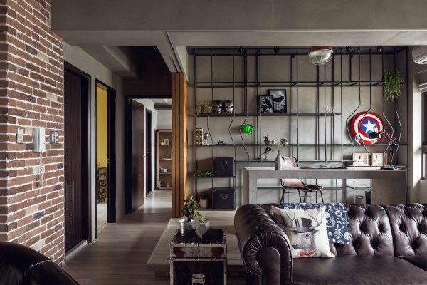 Marvel heroes themed living room with exposes brick and lots of different brown tones. It has a industrial touch and feels very manly and modern. The office space behind the English sofa  is very well integrated into the space.