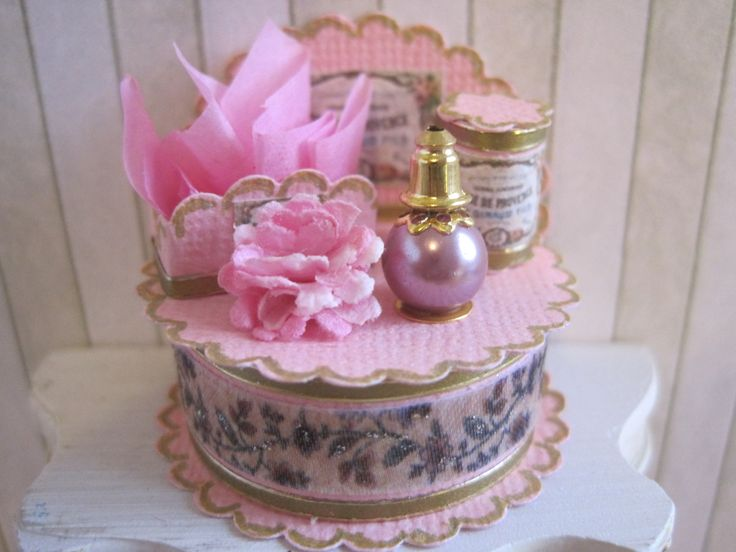 This pretty shabby chic perfume display stand would look great stood on a shop counter, or as a window display. Made from pink cardstock, the stand is filled with a variety of co-ordinating items, including a perfume bottle with gold detail, a box of soaps and a gift box lined with tissue. Finished with a gold trim, the piece has an elegant vintage feel. The stand measures approx 1.5 wide and 1.5 high, all the display goods are fixed in position and cannot be removed.  All my goods are OOAK…