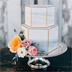 Hexagonal wedding cake with a marbled effect and gold piping