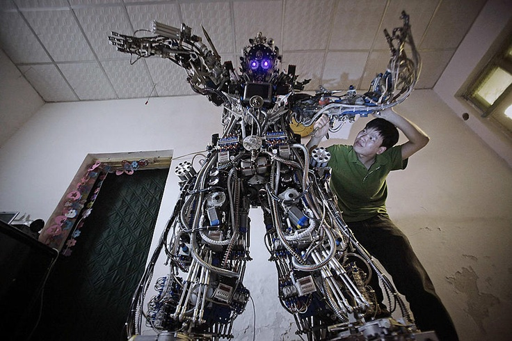 Chinese inventor Tao Xiangli modifies the circuits of his self-made robot at his house in Beijing.