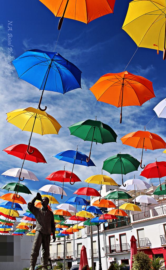 these umbrellas put out to create shade for residents and visitors alike by the municipal in torrox spain are also an amazing geometric public space art installation , a rainbow without rain Torrox Pueblo