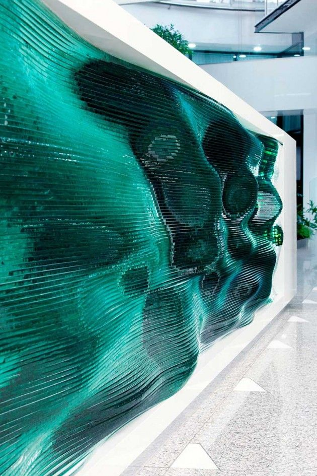 Glass layers make up this wavy reception desk by Tamás Ábel