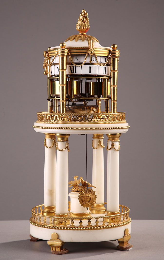 A late 18th century white marble and gilt bronze temple shape mantel clock composed of two levels.