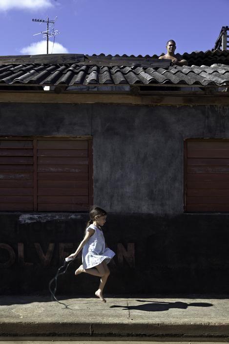 Cristina Garcia Rodero CUBA. Baracoa. Yadria Aliana Cala plays in front of her house while a man repairs the roof.