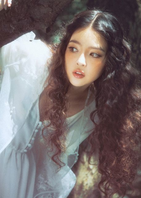 Doll face asian girl with orange blushed cheeks long curly wavy combination hair parted down the middle and glossed lips.