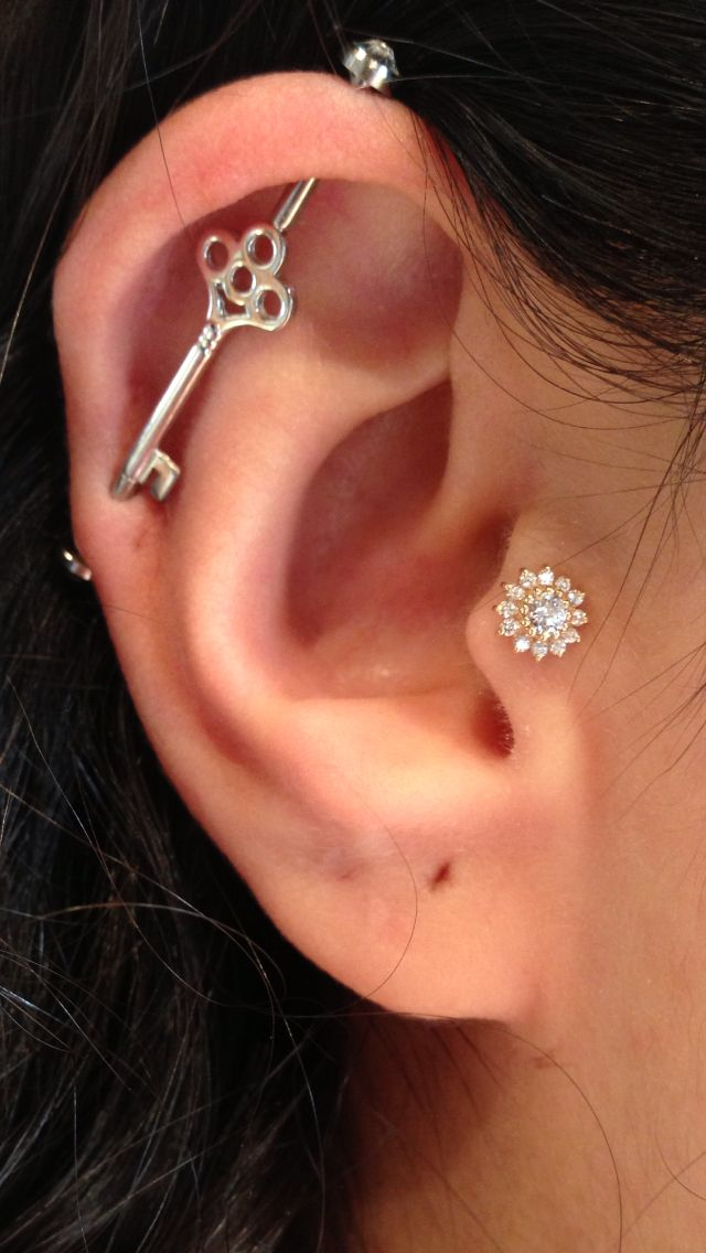 Bvla key industrial in white gold with a bvla yellow gold rose in her tragus. Done at club tattoo San Francisco