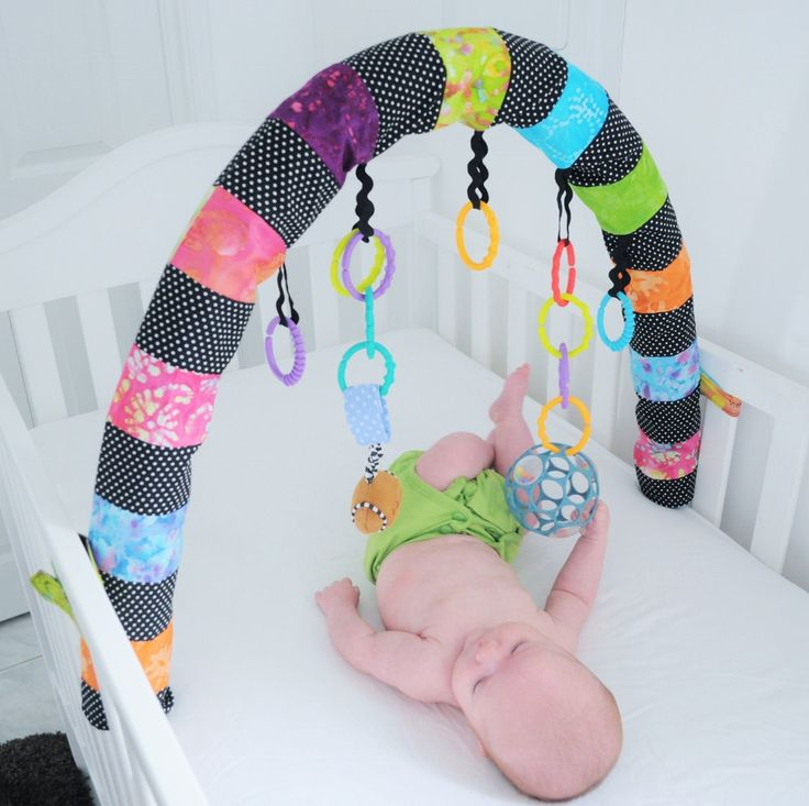 Could use a pool noodle covered in fabric. And shower curtain rings to attach toys.