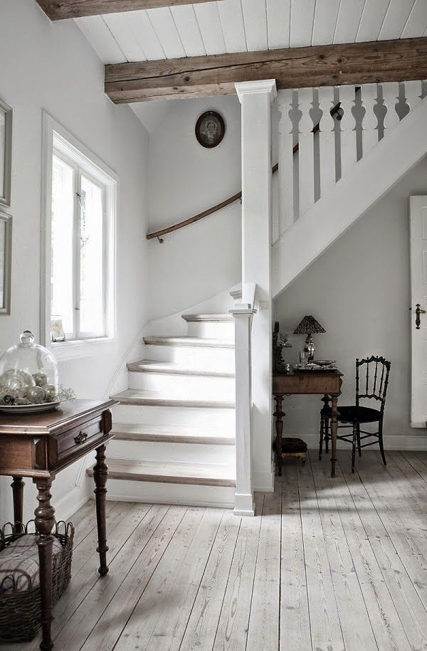 Lovely white on white stairway with wooden beams.