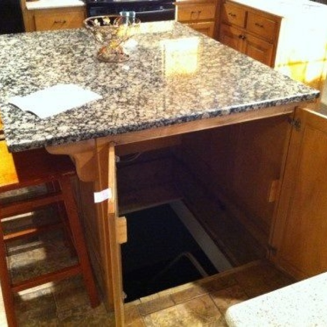 This would be awesome! A cellar entrance hidden under an island! Perfect for a wine cellar or gun closet!