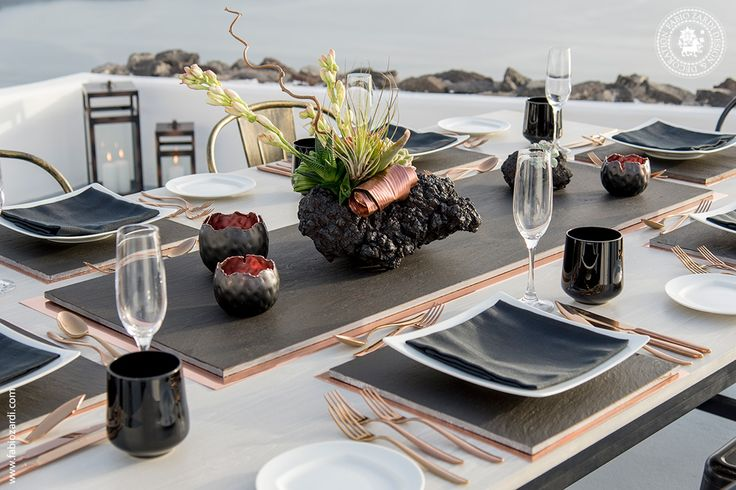 Private event, June 26th, 2014  Centerpieces in volcanic stone with flower arrangement. Black slate and copper. Bespoke copper cutlery.  Venue: Grace Hotel, Imerovigli, Santorini Design, concept & décor: Fabio Zardi Photo: Ventouris Photography