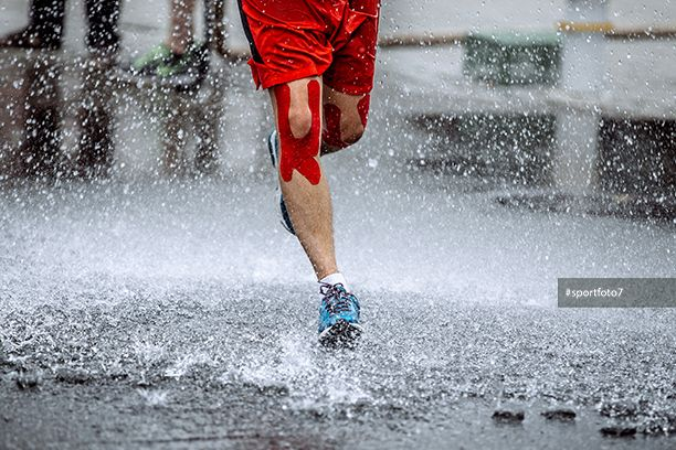 male athlete with tape on his knees running through a puddle of water