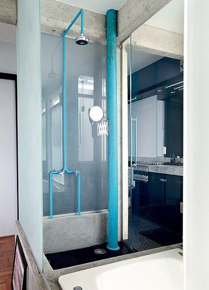 Na área do chuveiro deste banheiro, a tubulação e o cano de esgoto foram pintados de azul. O tom vibrante ganha ainda mais força na presença da estrutura de concreto. Projeto do arquiteto Diogo Oliva