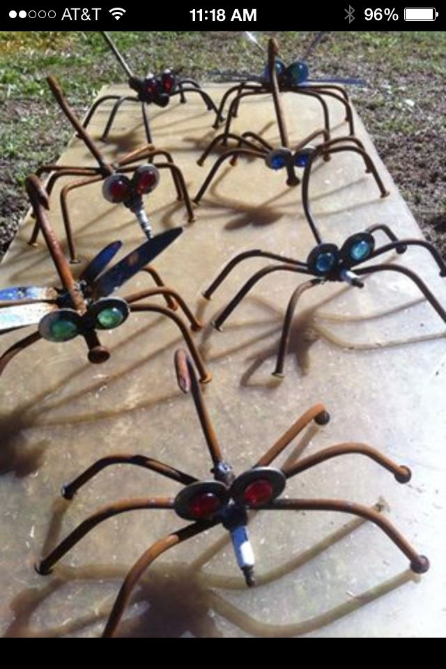 Welded insect yard art from tent stakes, nails and washers. Some are made of spark plugs and some have butter knife wings.
