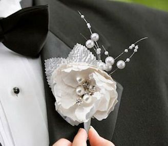 This attractive chic & shabby boutonniere is the perfect accent for a groom's jacket.A cream hand crafted paper flower houses pearls and rhinestones for a soft and elegant look. The boutonniere measur
