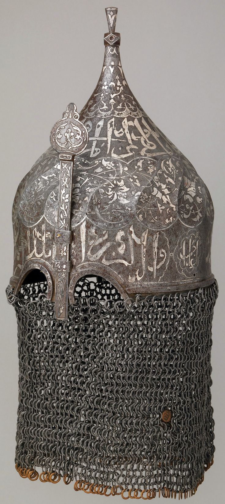 Indo-Persian turban helmet, late 15th century, Persian, Caucasian, or Anatolian, St Irene (Ottoman) arsenal mark, steel, silver, copper alloy, H. including mail 22 in. (55.9 cm); H. excluding mail 13 5/8 in. (34.6 cm); Wt. excluding mail 3 lb. 9 oz. (1616 g), Met Museum. Retains the alternating solid and round riveted mail aventail that protected the lower half of the face and neck.