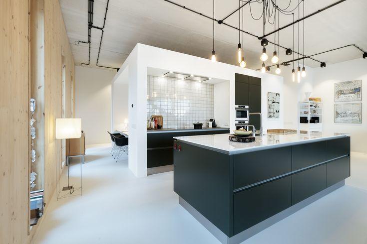 Grote room devider midden in de woning! Het volume herbergt een keuken, bijkeuken, werkplek en badkamer. De loft heeft een lichte en ruimtelijke uitstraling door de toepassing van een grijze gietvloer, houten wanden, wit stucwerk en een sfeervolle keuken met eiland. Ontwerp BNLA architecten | Fotografie Wim Hanenberg