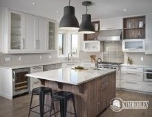 Custom White Kitchen with two-toned cabinets, oversized industrial pendants light the large island, wine fridge. | Custom built new home in Ambleside, Edmonton by Kimberley Homes  #interiordesign #newhomedesign #homedesign #newhome #customhome #yegre #buildwithkimberley #kimberleyhomes #kitchen #kitchenideas #kitcheninspo #kitchenreno #whitekitchen