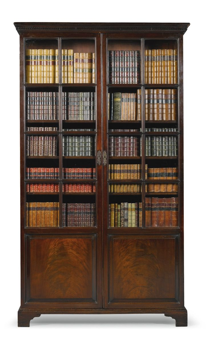 A George II mahogany bookcase circa 1750 with a moulded dentil cornice above a pair of cupboard doors with astragal glazing to the top and fielded panels below, enclosing adjustable shelves, (one now fixed),  on bracket feet