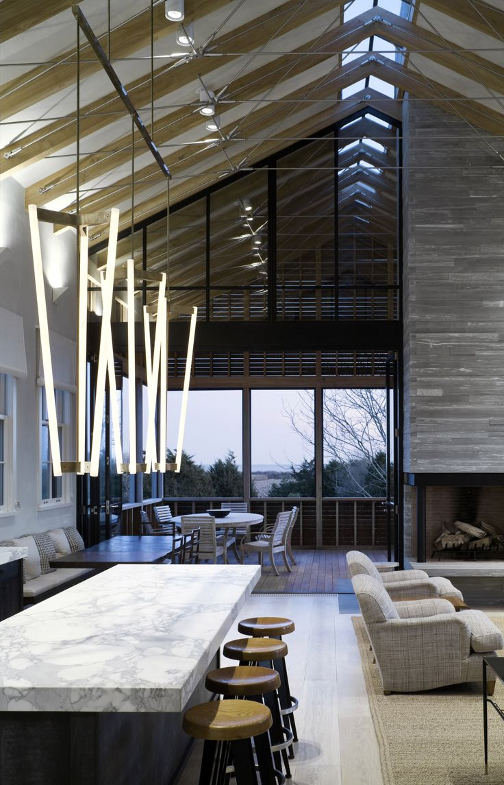 "A spacious home in the Hamptons, New York, by Leroy Street Studio features wooden screens that soften the building's appearance and provide a ""gauzy translucence"" at night."