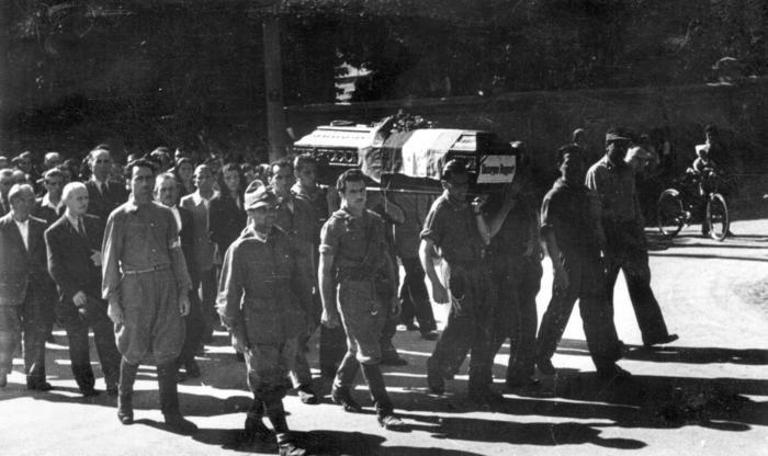 La sfilata del corteo funebre, aperto dalle formazioni partigiane, che accompagna le salme dei partigiani vimercatesi dal cimitero di Arcore a quello di Vimercate il 13 maggio 1945: le bare dei caduti portate a spalla dai compagni.