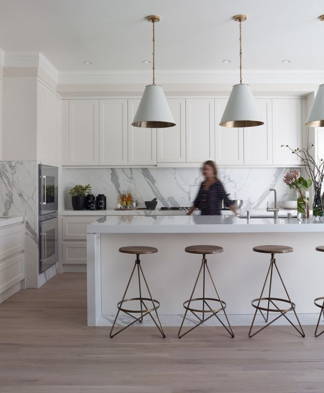 In this Greenwich Street home kitchen, bookmatched Calcutta Oro backsplashes add depth and beauty against the elongated symmetry of the kitc...