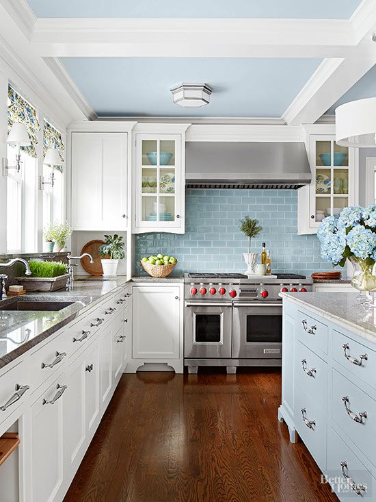 Abundant lower drawers with brushed silver handles more than compensate for the lack of upper cabinets in this spacious kitchen. A light color palette and glass-front doors keep the room bright and airy. Mixing blue and white cabinetry conveys classic cottage style.