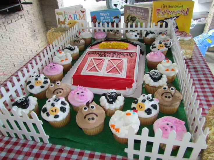 """This was the birthday cake for my two year olds farm animal theme party. The base my husband made by covering plywood with felt and adding white fencing from Hobby Lobby.  We added a protective layer of felt that we removed after the cake and it now serves as a """"pasture"""" for her to play with her farm animal toys."""