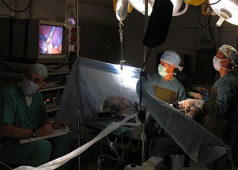 Założenie opaski wykonuje się metodą laparoskopową. Chirurdzy operują narzędziami laparoskopowymi a wnętrze brzucha obserwują na monitorze TV. Dla dobrej widoczności na sali operacyjnej jest ciemno.
