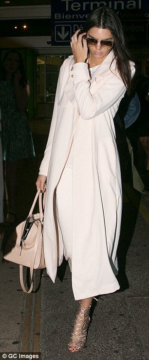 Classy coat: The 19-year-old model cut a stylish silhouette in a long cream-coloured coat with strappy bronze heels as she made her way through the airport terminal