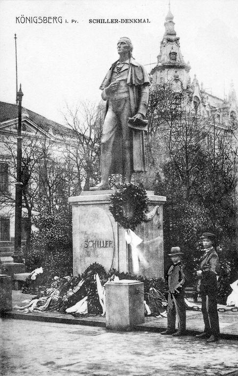 """Königsberg i. Pr. - Buchhandlung Gräfe & Unzer am Paradeplatz 6, im Vordergrund das Schillerdenkmal: """"Das Alte stürzt, es ändert sich die Zeit und neues Leben blüht aus den Ruinen"""", ca. 1916"""