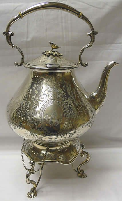 Victorian Silver Plated Kettle on Stand.  A decorative antique hot water kettle engraved with flowers, foliage and scrolls. There is a crest with motto to the front. With shaped carrying handle and original ivory insulators. The kettle is attached by 2 chains and keys to its circular stand.