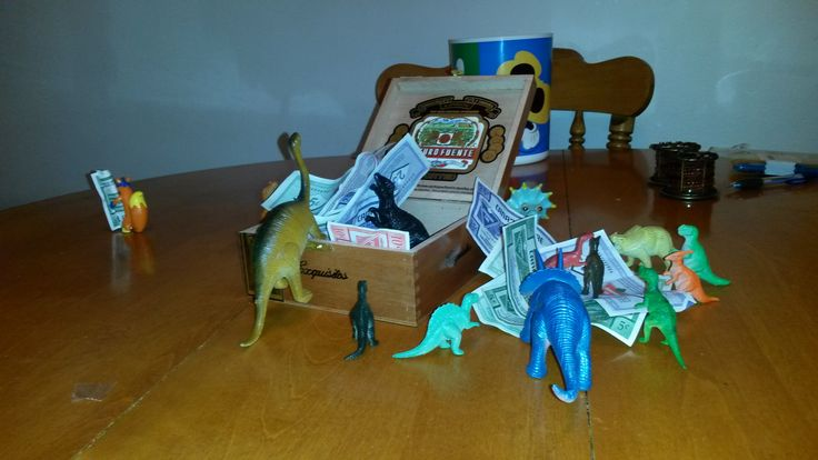 """November 8, 2014: The dinos discovered my son's """"money box,"""" an old cigar box filled with Canadian Tire money. Swiper is being a ltitle swiper once again!"""