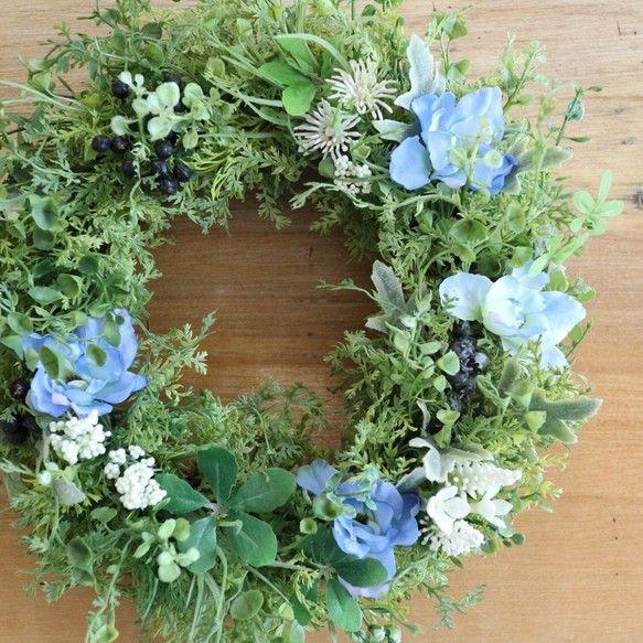 様々な形のグリーンをふんだんに使用し立体感を出した、ボリュームのあるリースです。爽やかなブルーのデルフィニュームをポイントに置いて、ブラックベリーや白い小花を控えめに加えました。本物に近い自然な色合いの素材を使用していますので、造花は苦手…という方にもオススメです。素材は全てアーティフィシャルフラワーを使用していますので、屋外のドアなどでも安心して飾ることができます。ーーーーーーーーーーーーーーーーーーー◯サイズ: 直径29cm 厚さ8cm◯素材:アーティフィシャルフラワー(ポリエチレン)◯ラッピング:有料ラッピングでは専用のクラフトリースBOXにお入れしてリボンお付けします。無料ラッピングではセロファンでの簡易ラッピングとなります。ーーーーーーーーーーーーーーーーーーー※できるだけ商品の色合い・風合いをそのままにお伝えできるよう努めておりますが、お使いのブラウザの環境により多少の色の違い等が生じる場合がございます。ご理解くださいませ。