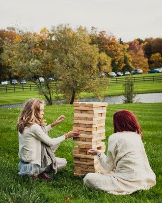 Create a life-sized Jenga game for guests to play at the reception.