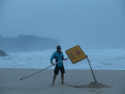A lifeguard at Bronte Beach puts up a 'beach closed' sign after winds and rain battered Sydney on 29 January, 2013.