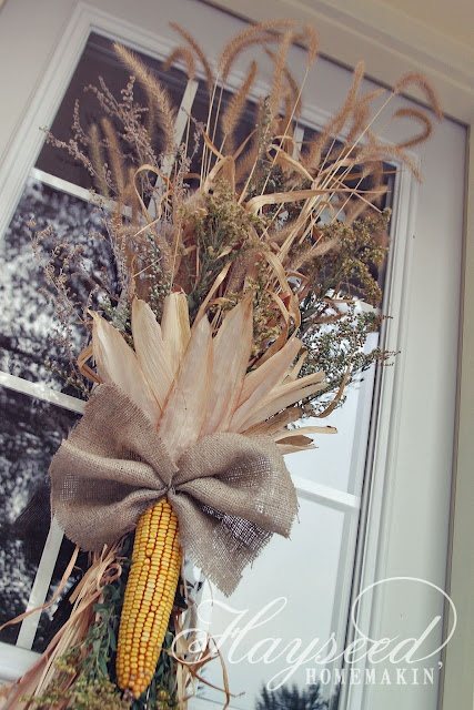 Fall Decor with burlap, corn, and dried grasses. A beautiful way to dress up a front door to last from September thru November. Just add a few black plastic spiders or black deco mesh for October (boo!).