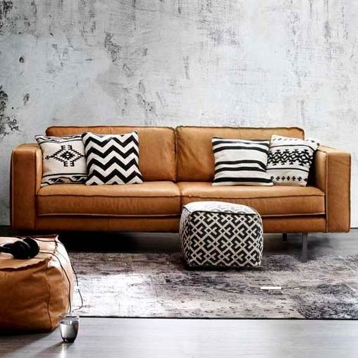 Brown leather sofa with black and cream pillows