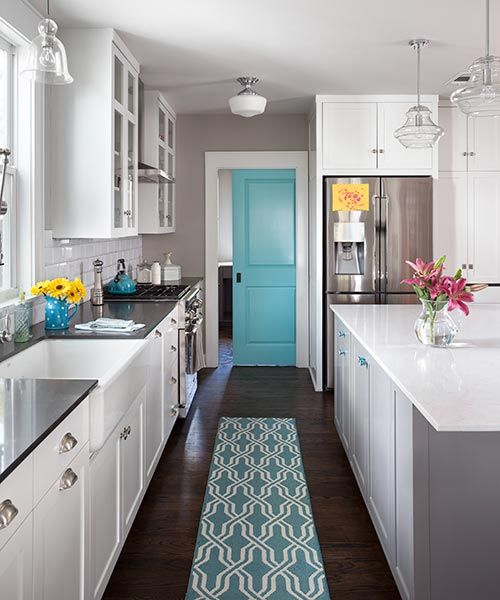 A pocket door, punched up with aqua paint, closes off this laundry room.